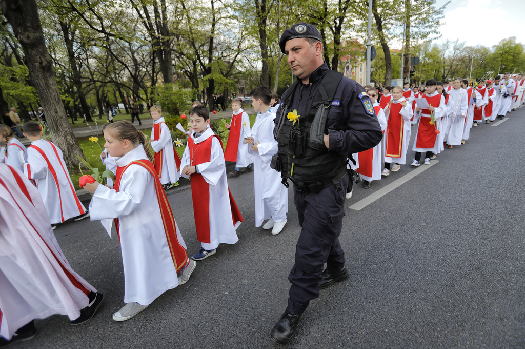 In this Sunday, April 9, 2017, picture a gendarme with a flowers attached to his uniform walks next to Catholic children taking part in...