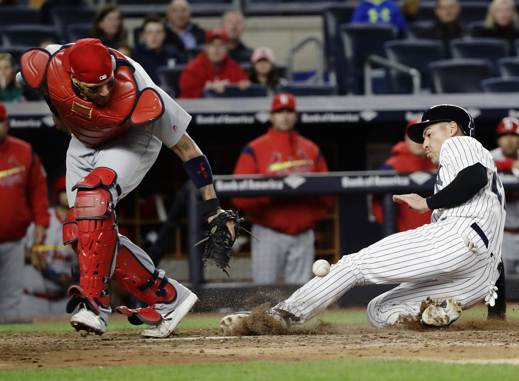 New York Yankees' Jacoby Ellsbury, right, scores on a throwing error by St. Louis Cardinals' Kolten Wong as catcher Yadier Molina field...