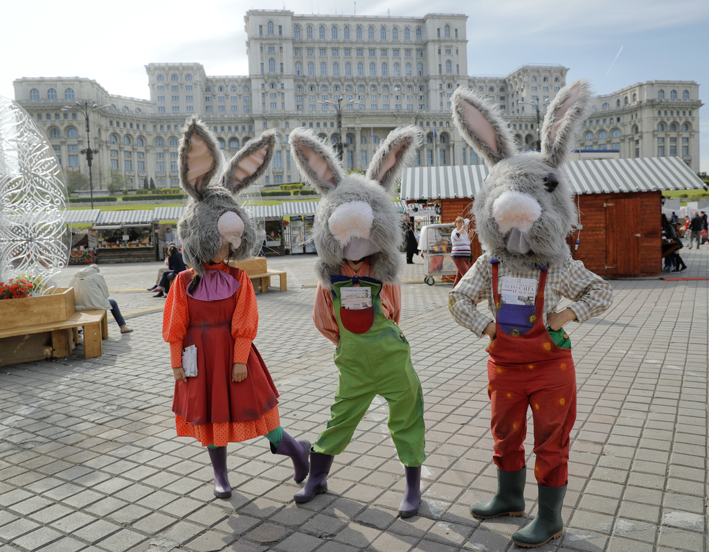 In this Thursday, April 13, 2017, picture entertainers wearing rabbit costumes strike a pose backdropped by the communist era built Hou...