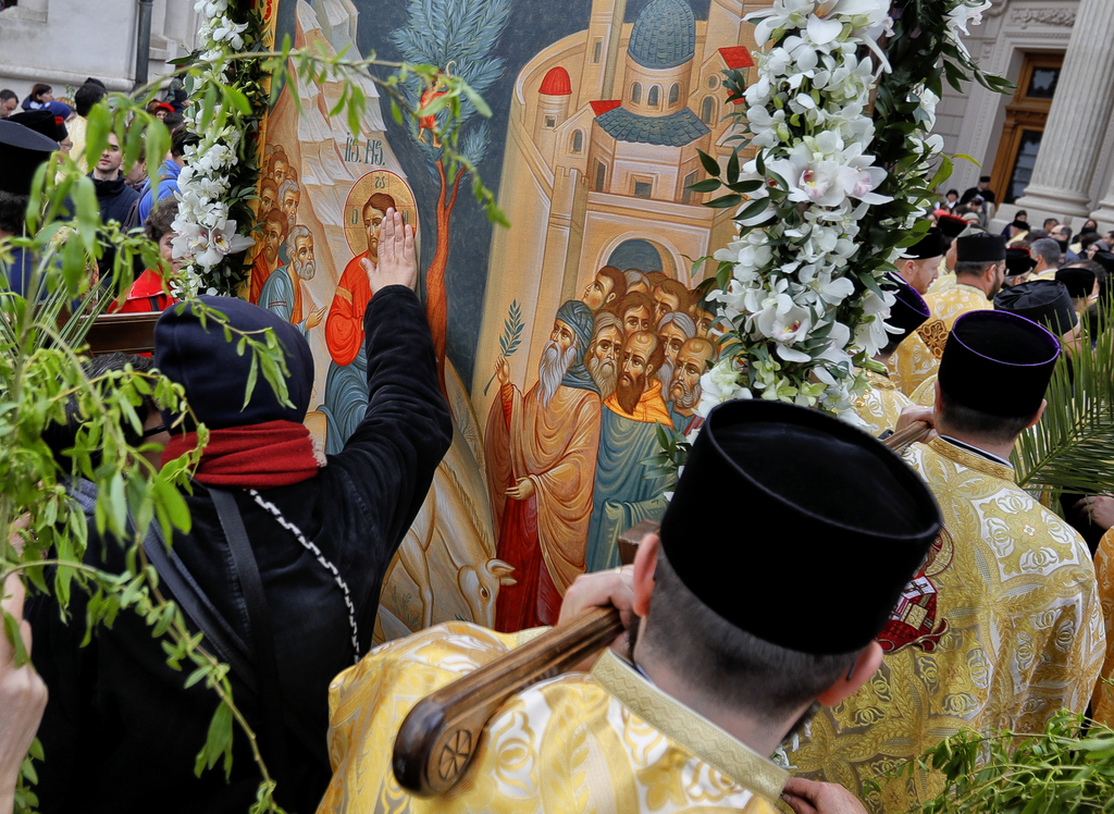 In this Saturday, April 8, 2017, picture a woman touches a large icon carried by Romanian Orthodox priests after a service ahead of Pal...