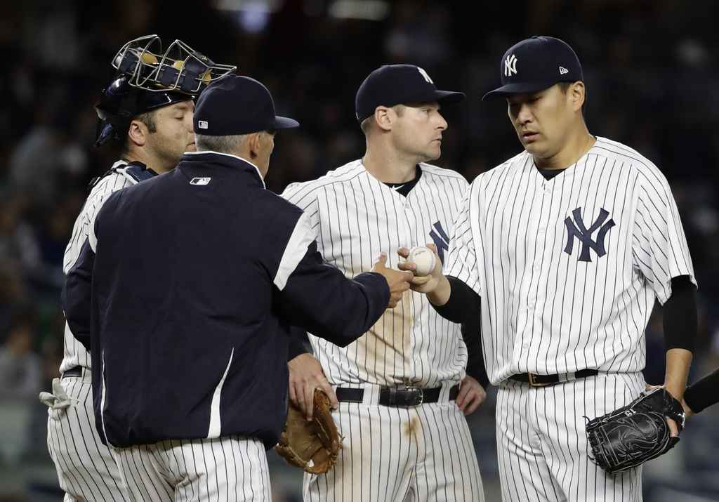 New York Yankees starting pitcher Masahiro Tanaka, right, of Japan, hands the ball to manager Joe Girardi, left, as he leaves during th...