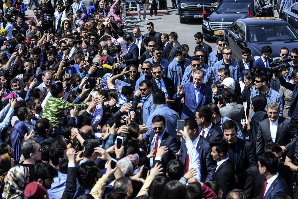 Turkey's President Recep Tayyip Erdogan, center right,  waves to supporters as he leaves a polling station in Istanbul, on Sunday, Apri...