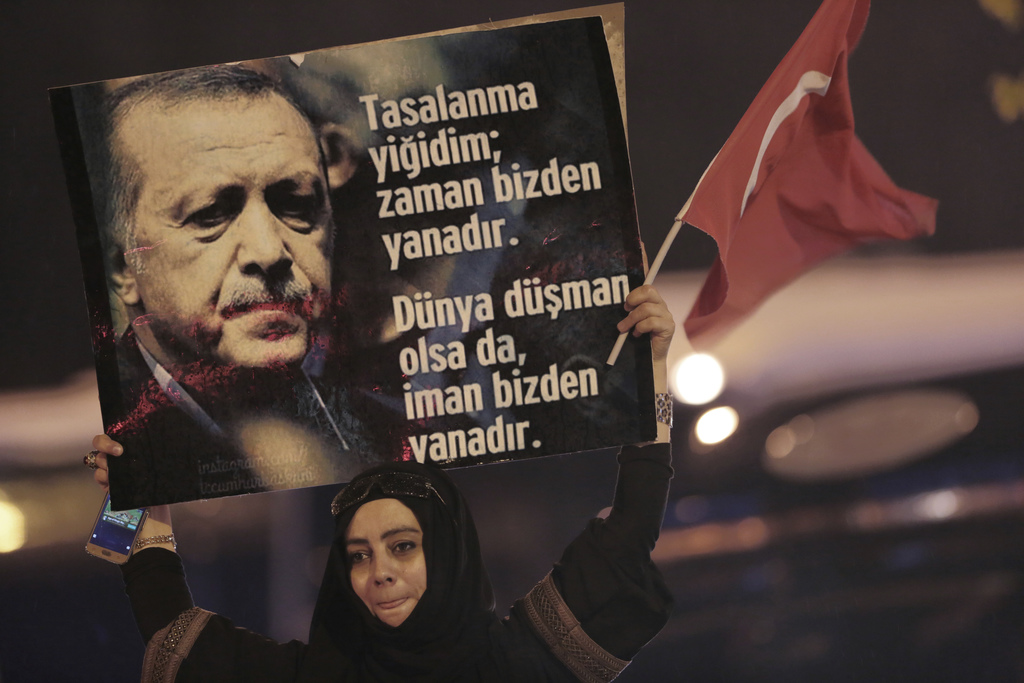 """A supporter of President Recep Tayyip Erdogan holds a placard that reads """"don't worry, the world can be our enemy """" in Ankara, Turkey, ..."""