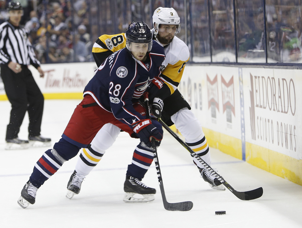 Columbus Blue Jackets' Oliver Bjorkstrand, left, of Denmark, and Pittsburgh Penguins' Olli Maatta, of Finland, chase the puck during th...