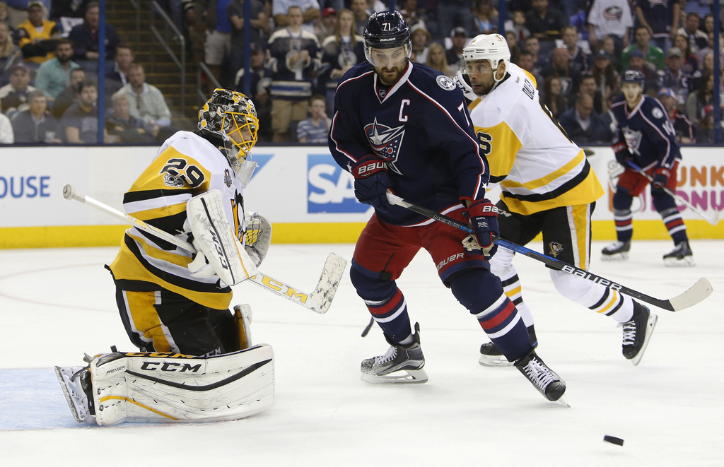 Pittsburgh Penguins' Marc-Andre Fleury, left, makes a save against Columbus Blue Jackets' Nick Foligno during the second period of Game...