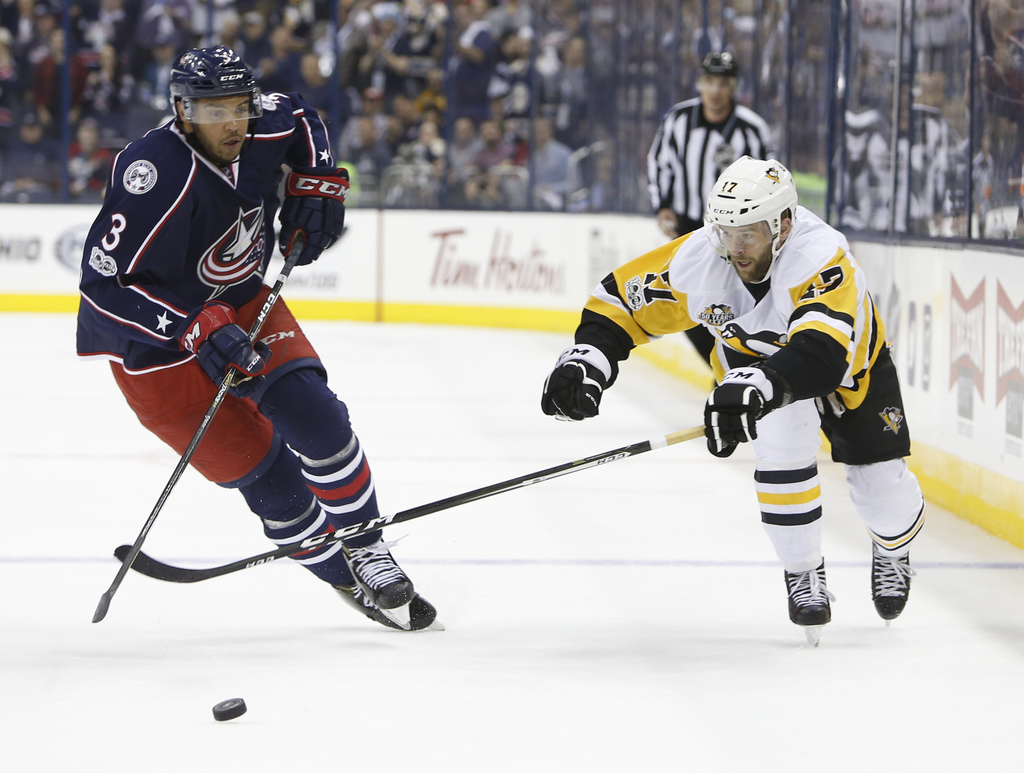 Columbus Blue Jackets' Seth Jones, left, knocks the puck away from Pittsburgh Penguins' Bryan Rust during the first period of Game 4 of...