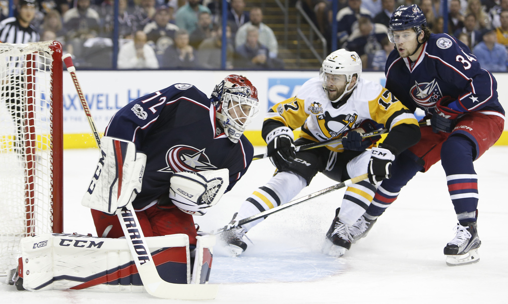 Columbus Blue Jackets' Sergei Bobrovsky, left, of Russia, makes a save as teammate Josh Anderson, right, and Pittsburgh Penguins' Bryan...