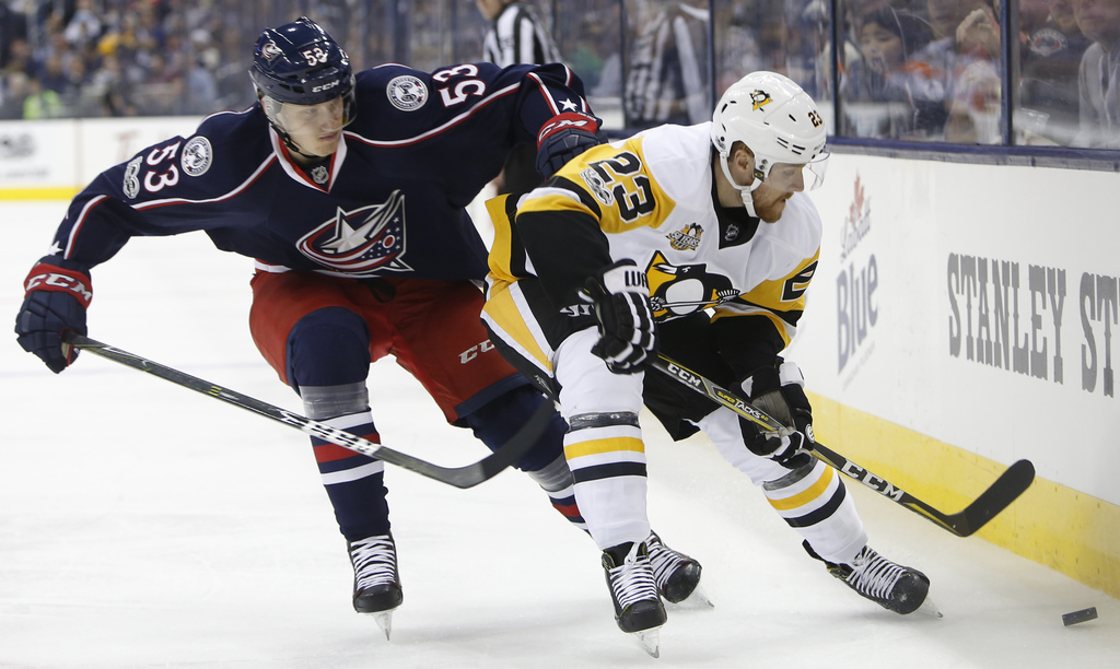 Columbus Blue Jackets' Gabriel Carlsson, left, of Sweden, and Pittsburgh Penguins' Scott Wilson chase the puck during the first period ...