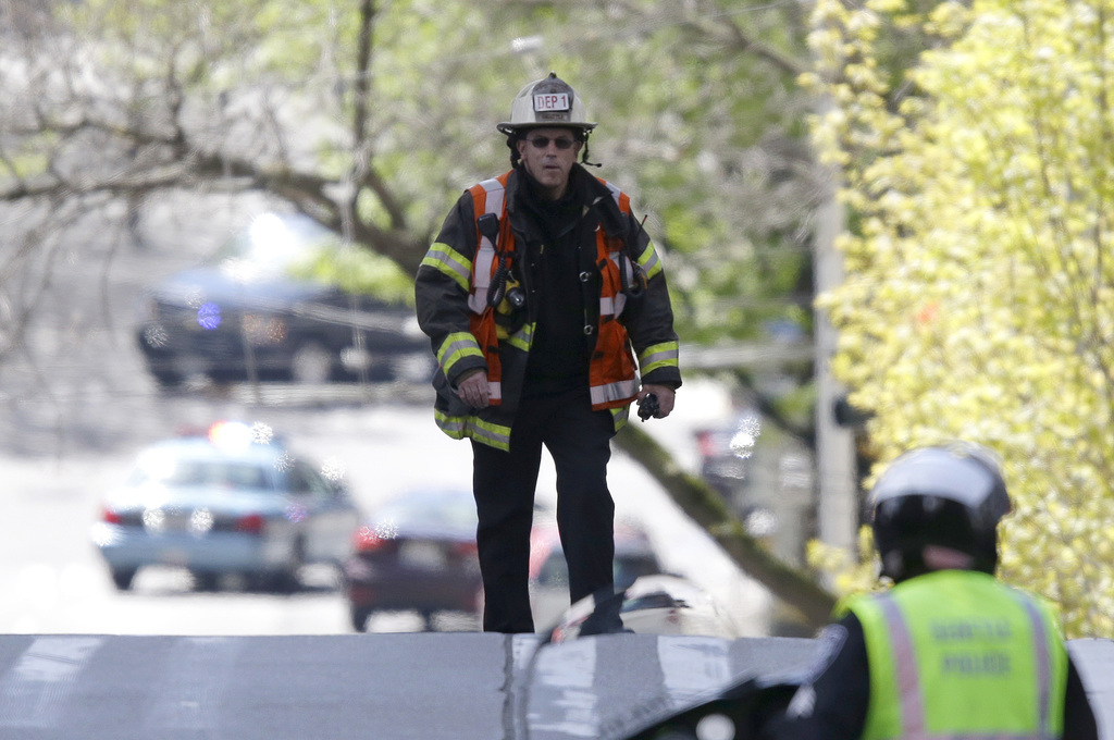 A Seattle firefighter walks near the scene of a shooting involving several police officers in downtown Seattle, Thursday, April 20, 201...