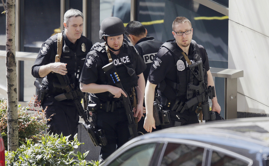 Seattle Police officers walk with guns near the scene of a shooting involving several police officers in downtown Seattle, Thursday, Ap...