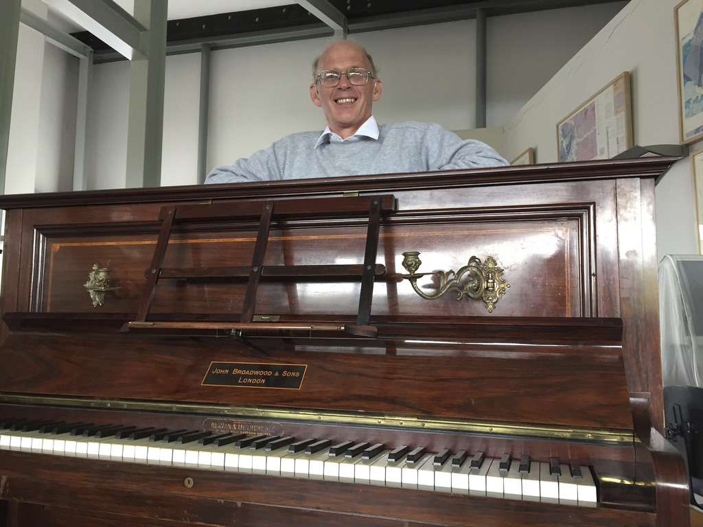 Piano tuner Martin Backhouse with the piano where he found a stash of gold, smiles in Ludlow Museum in Ludlow, England Thursday April 2...