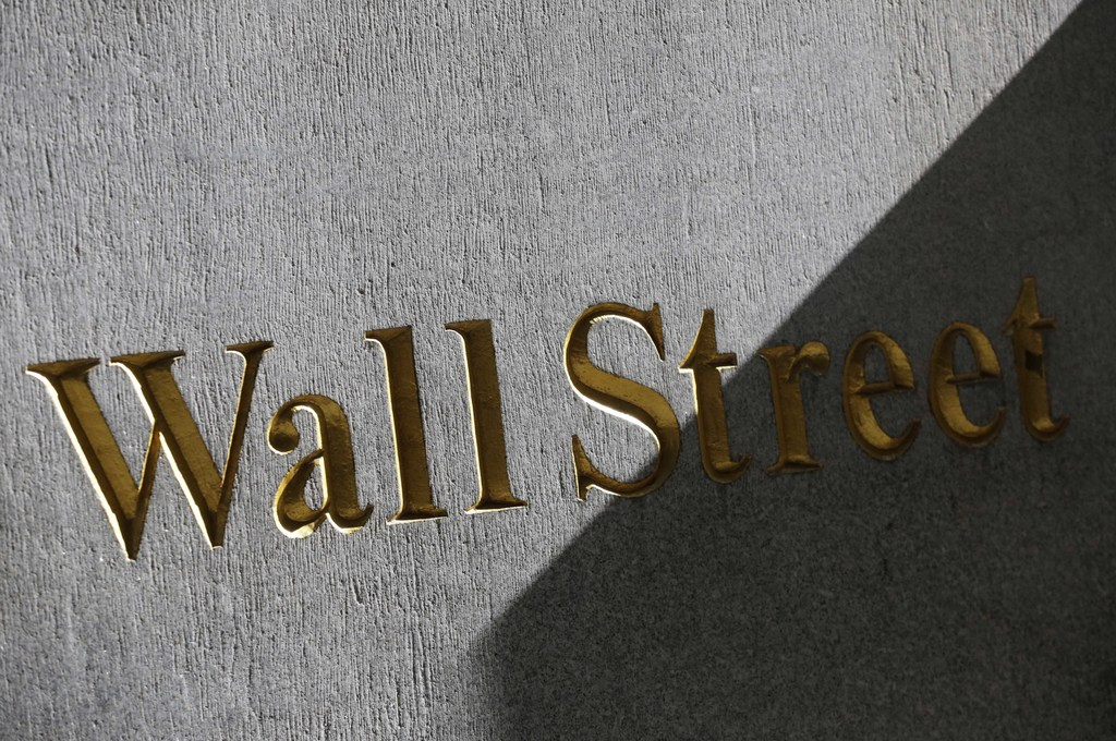 FILE - This March 4, 2013, file photo shows a sign for Wall Street on the side of a building near the New York Stock Exchange. U.S. stocks perked high