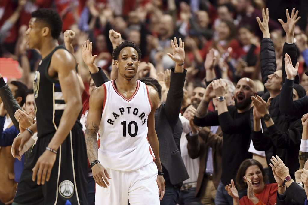 Fans cheer as Toronto Raptors guard DeMar DeRozan (10) reacts after hitting a three-pointer against the Milwaukee Bucks during the seco...