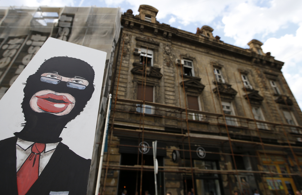 A protester holds a banner depicting masked Serbian Prime Minister Aleksandar Vucic during a protest in Belgrade, Serbia, Tuesday, Apri...