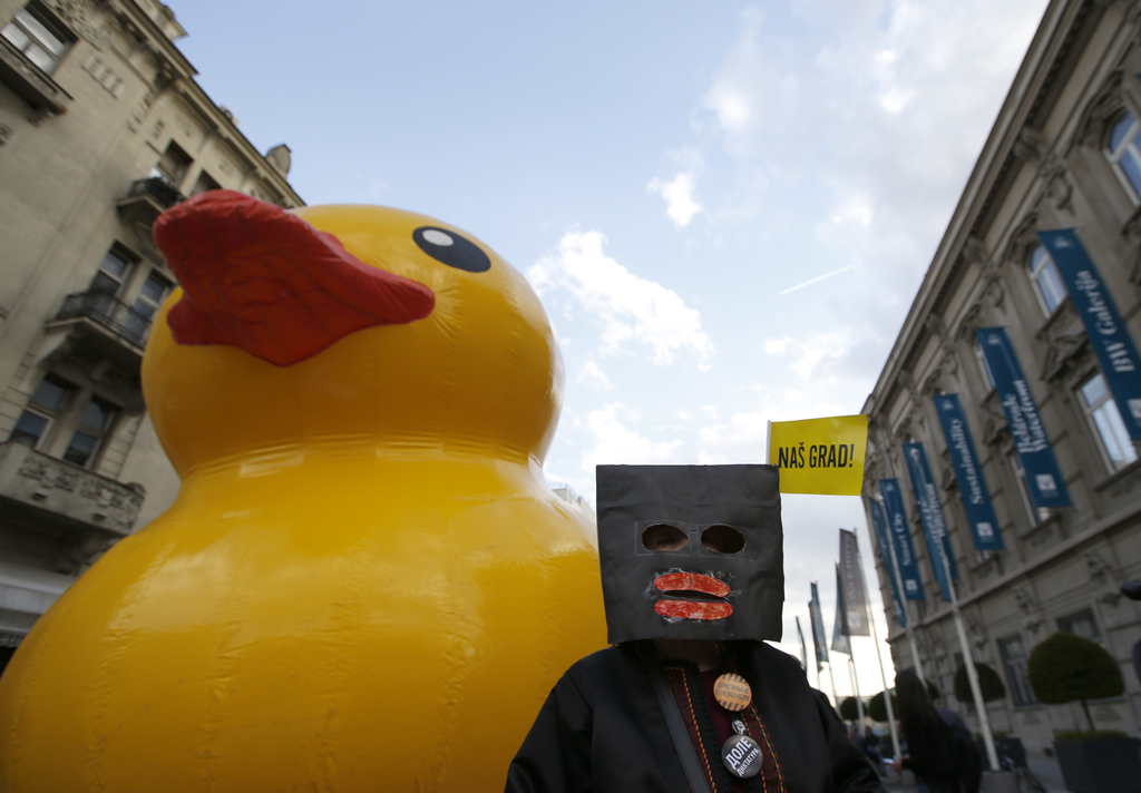 A woman wearing a mask stands in front of a giant yellow rubber duck, a mascot of a group of people criticizing the Belgrade waterfront...
