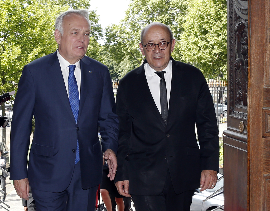 Outgoing French Foreign Minister Jean-Marc Ayrault escorts Jean-Yves Le Drian, right, who was named as Foreign Minister and Minister fo...