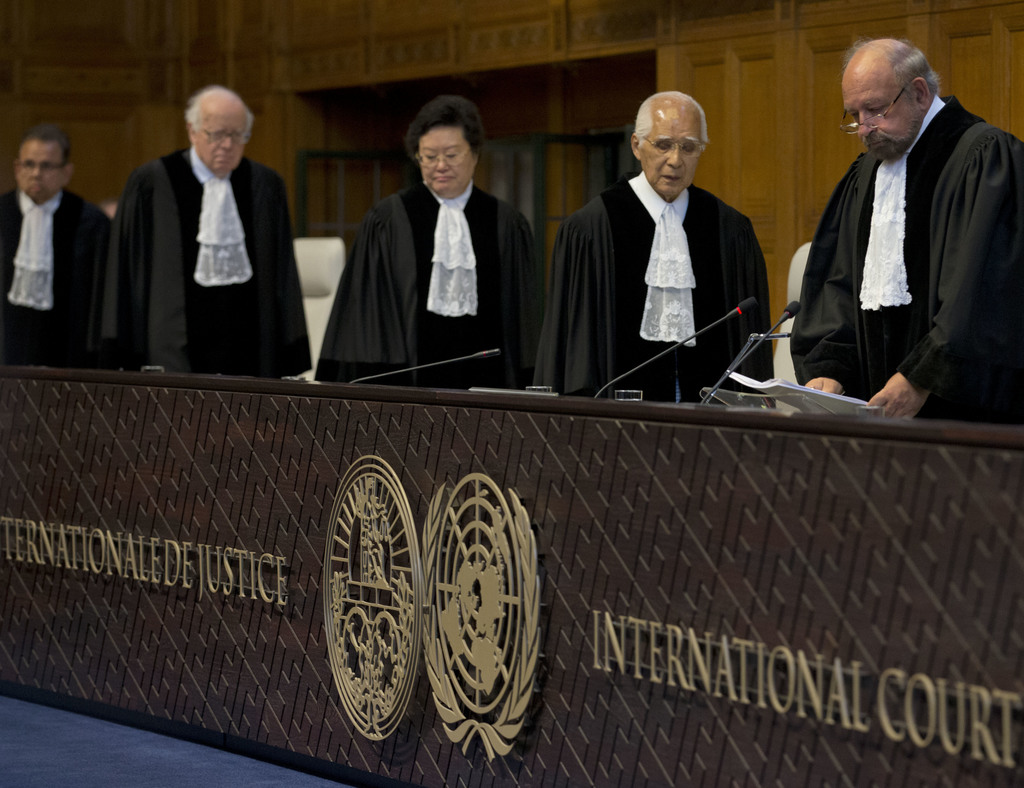 Presiding judge Ronny Abraham of France, right, enters to read the World Court's verdict in the case brought by India against Pakistan