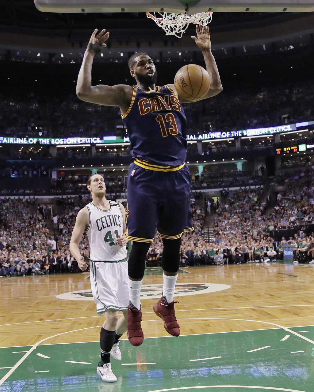 Cleveland Cavaliers center Tristan Thompson (13) follows through on a dunk in front of Boston Celtics center Kelly Olynyk (41) during t...