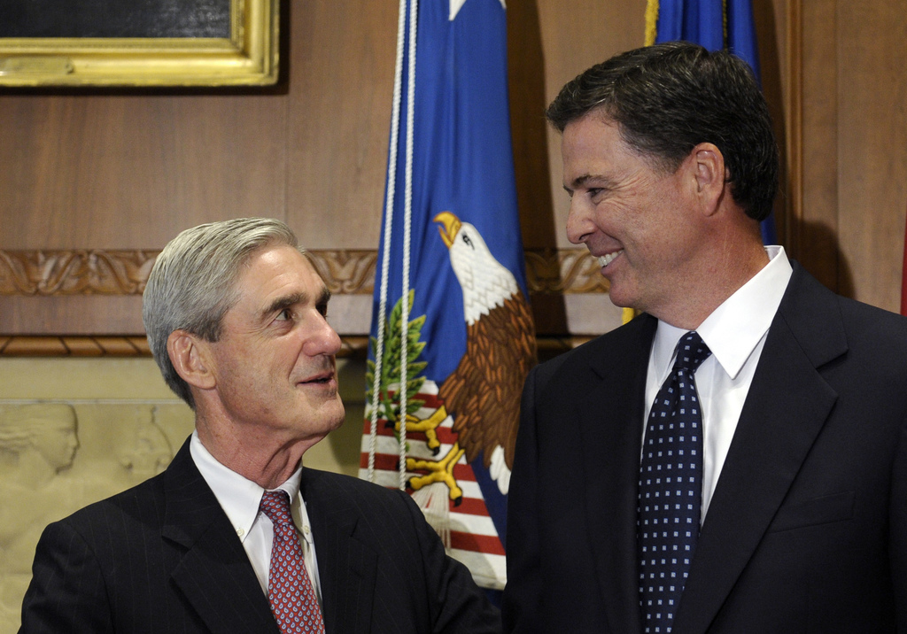 FILE - In this Sept. 4, 2013, file photo, then-incoming FBI Director James Comey talks with outgoing FBI Director Robert Mueller before...
