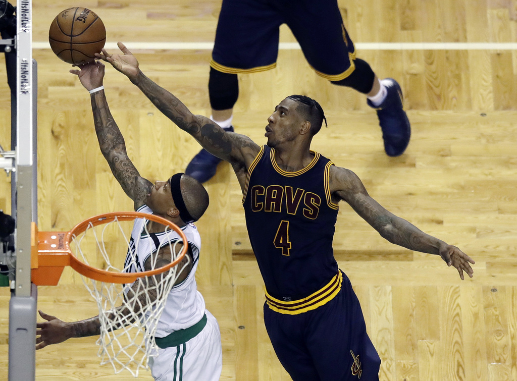 Cleveland Cavaliers guard Iman Shumpert, right, tips the ball as Boston Celtics guard Isaiah Thomas shoots during the second quarter of...