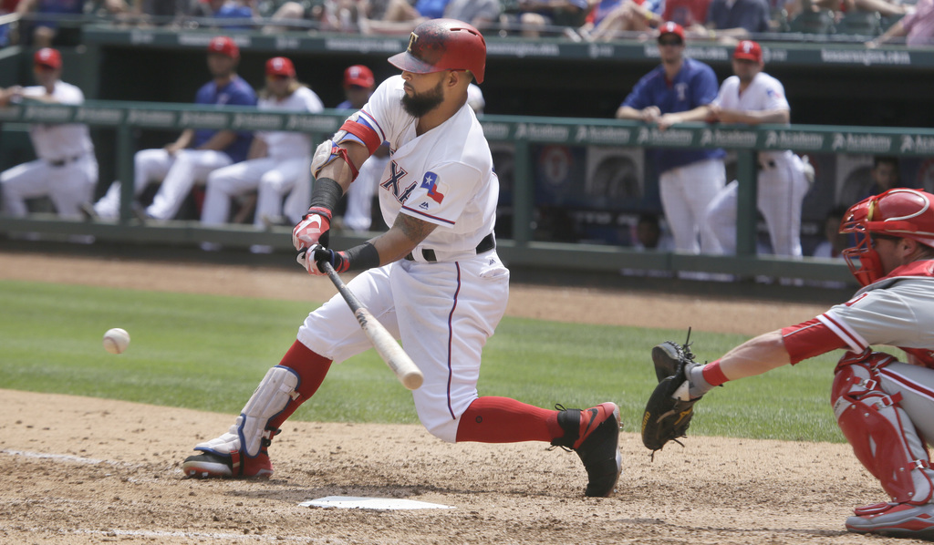Texas Rangers' Rougned Odor, left, hits an RBI single in front of Philadelphia Phillies catcher Andrew Knapp during the fifth inning of