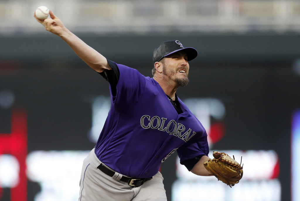 Colorado Rockies relief pitcher Chad Qualls throws to a Minnesota Twins batter during the sixth inning of the second game of a baseball