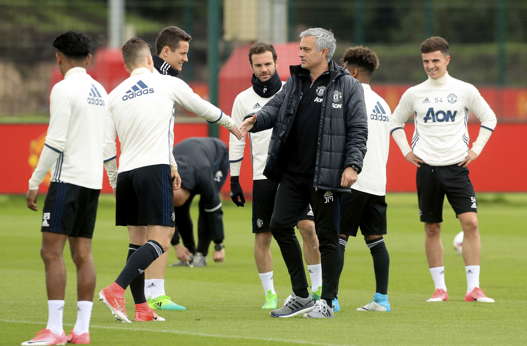 Manchester United manager Jose Mourinho, center, greets his players during a training session at the Aon Training Complex, Carrington, ...