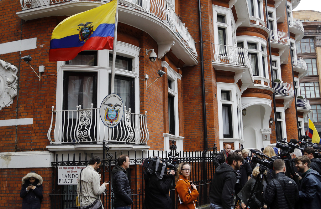 People gather outside the Ecuadorian embassy in London, Friday May 19, 2017. Sweden's top prosecutor says she is dropping an investigat...