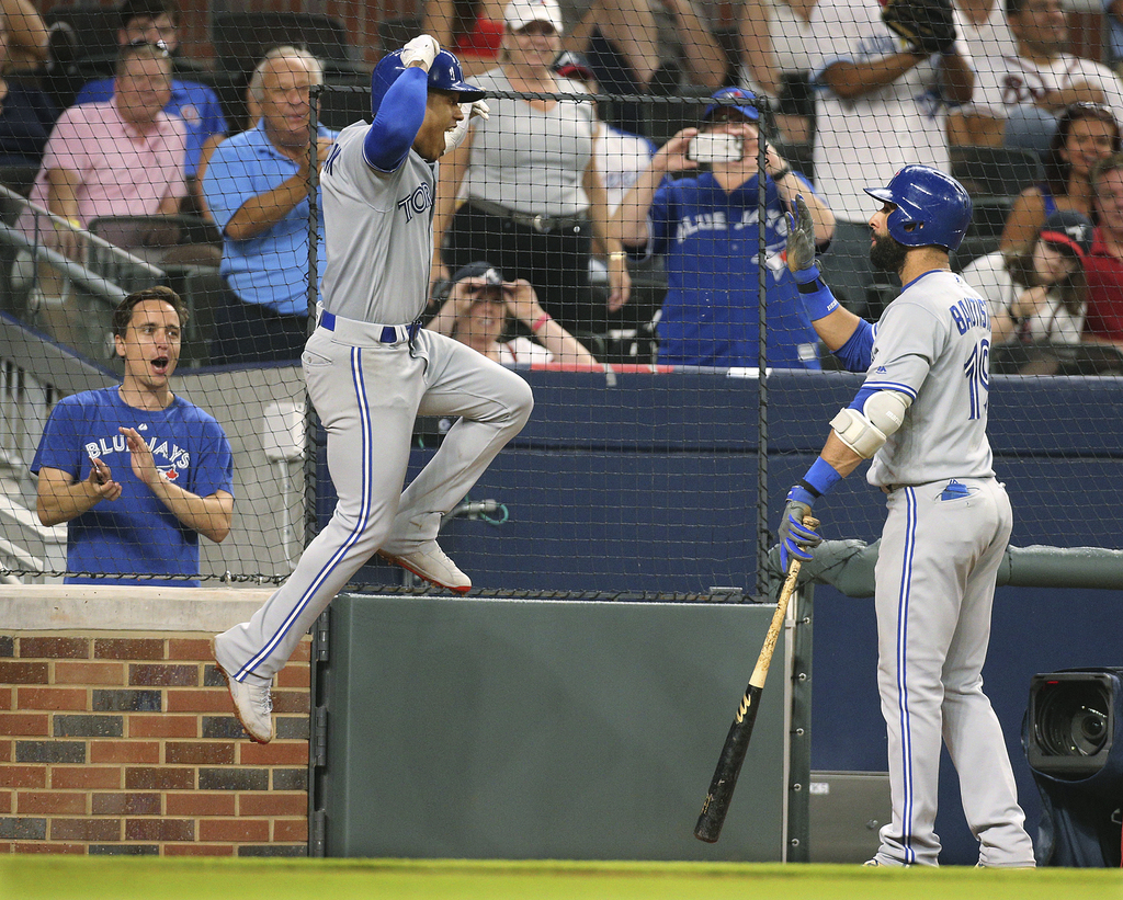 Toronto Blue Jays pitcher Marcus Stroman leaps while celebrating his solo home run against the Atlanta Braves with Jose Bautista during