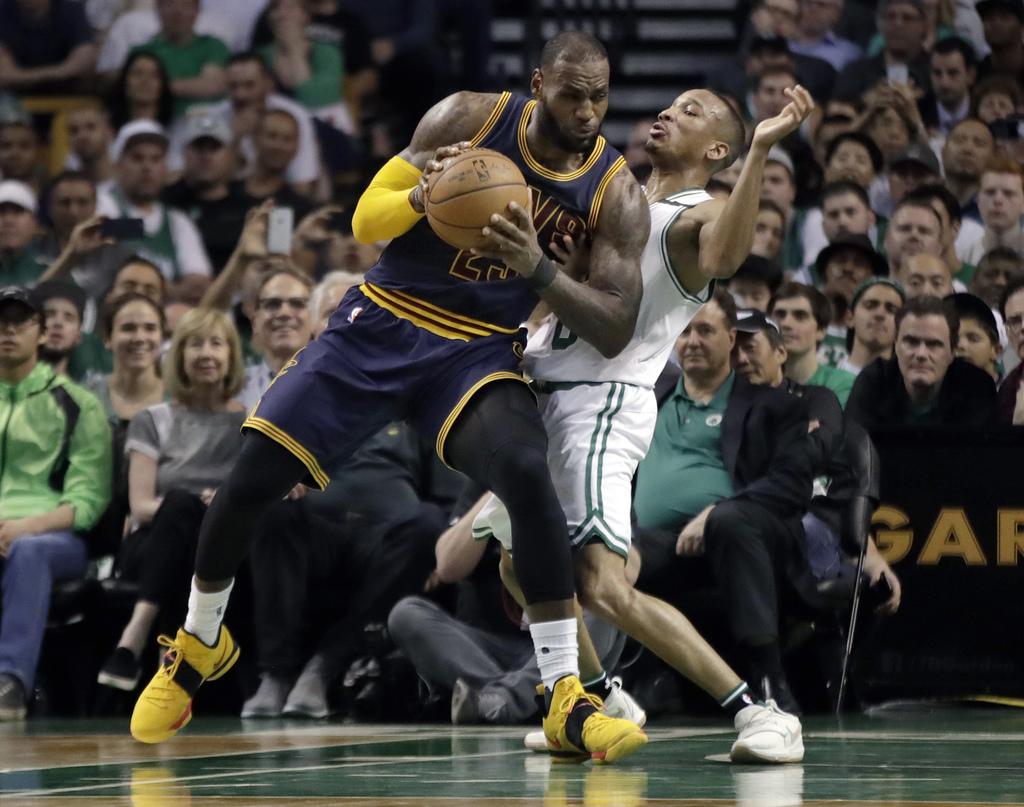 Cleveland Cavaliers forward LeBron James, left, muscles his way to the basket as Boston Celtics guard Avery Bradley, right, tries to de...