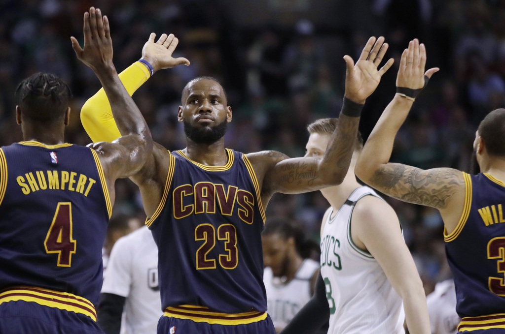 Cleveland Cavaliers forward LeBron James trades high-fives with teammates Iman Shumpert, left, and Deron Williams, right, during the fi...