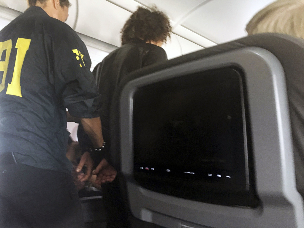 In this photo provided by Donna Basden, a man is escorted off an American Airlines flight after it landed in Honolulu, Friday, May 19, ...