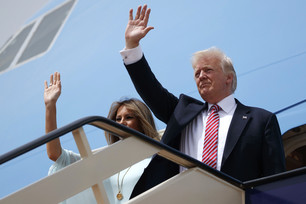 U.S. President Donald Trump, right, and first lady Melania Trump wave as they board Air Force One for Israel, the next stop in Trump's ...