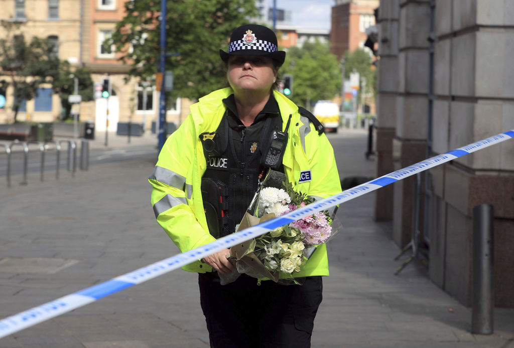 A police officer carries a floral tribute close to the Manchester Arena, the morning after a suicide bomber killed more than a dozen pe...