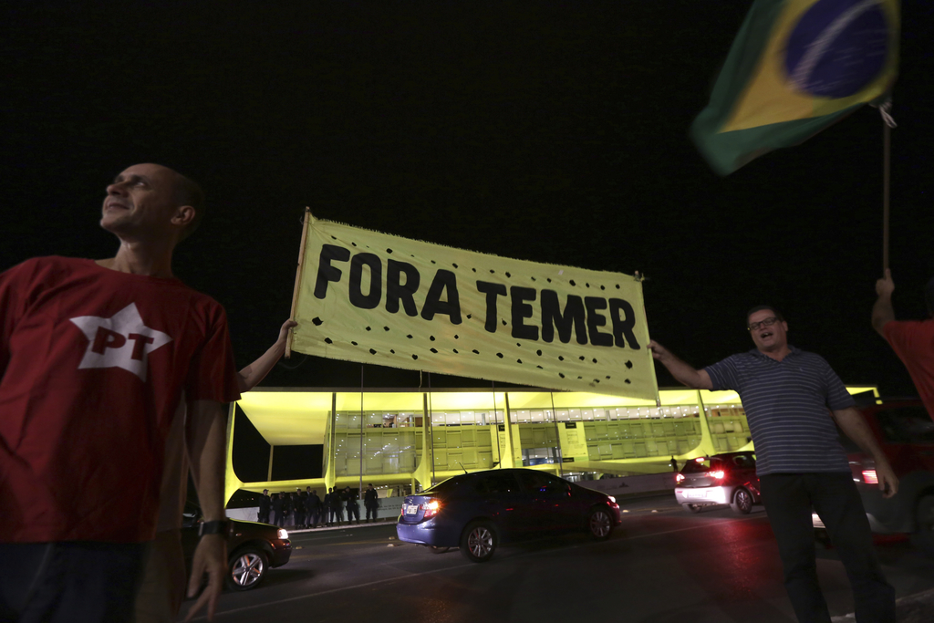 """Demonstrators shout slogans and carry poster written in Portuguese that read """"Temer Out"""" in front of the Planalto Presidential Palace, ..."""