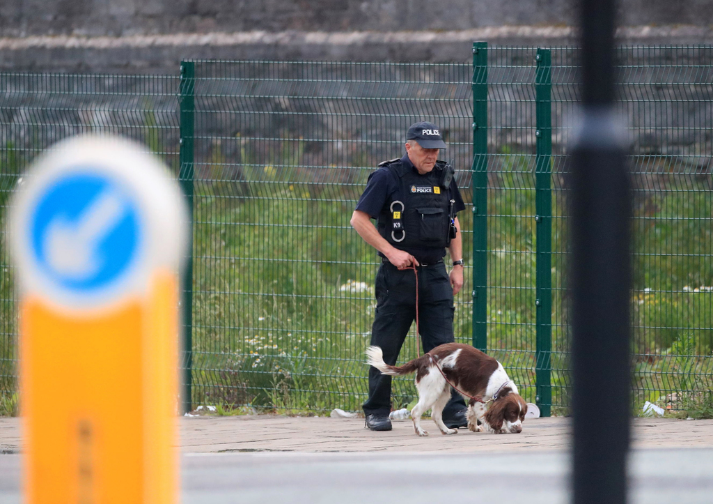 A police officer with a sniffer dog patrols near the Manchester Arena in Manchester, England Tuesday, May 23, 2017. An explosion struck...
