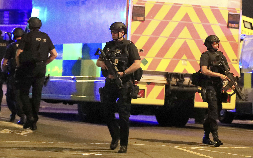 Armed police respond after reports of an explosion at Manchester Arena during an Ariana Grande concert in Manchester, England, Monday, ...