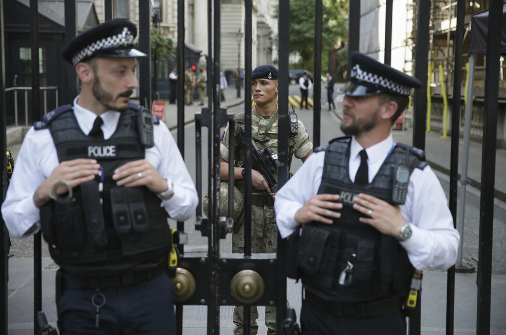 A soldier joins armed police officers guarding Downing Street in London, Wednesday May 24, 2017. Britons will find armed troops at vita...