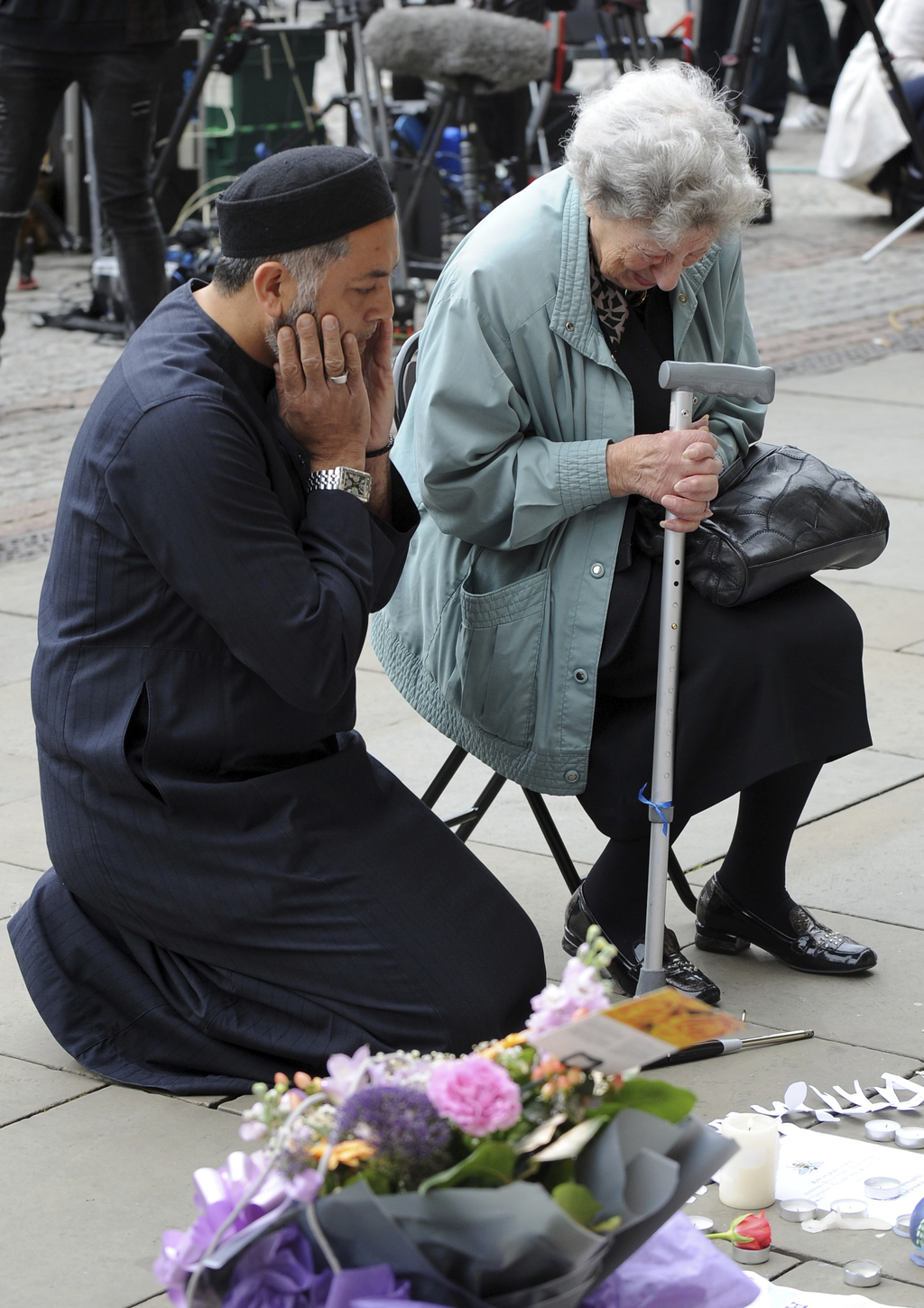 Renee Rachel Black, right, and Sadiq Patelin pray in front of flower tributes at Albert Square central Manchester, England Wednesday Ma...
