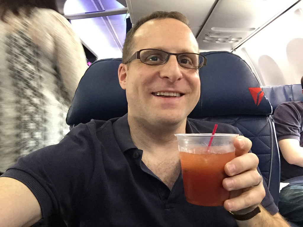 In this Friday, May 12, 2017, photo, Associated Press journalist Scott Mayerowitz enjoys a Bloody Mary while sitting in first class on ...