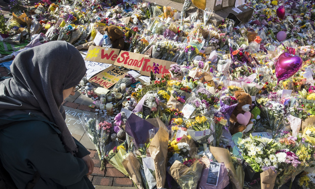 A woman looks at the floral tributes and messages left for the victims of the concert blast, during a vigil at St Ann's Square in centr...