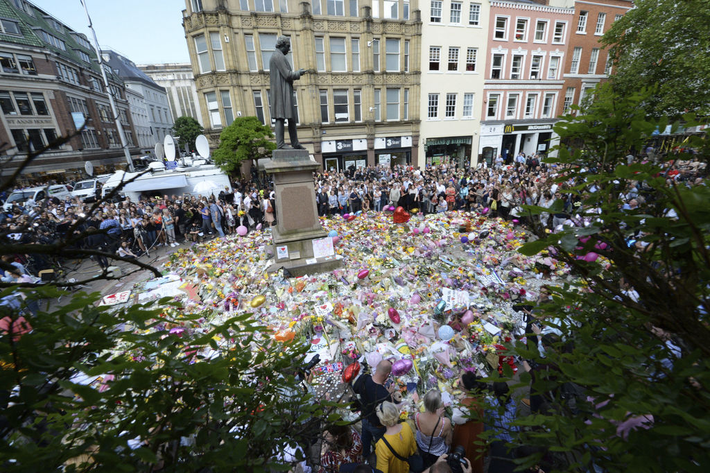 People hold a minute of silence in a square in central Manchester, England, Thursday, May 25, 2017, for the victims of the suicide atta...