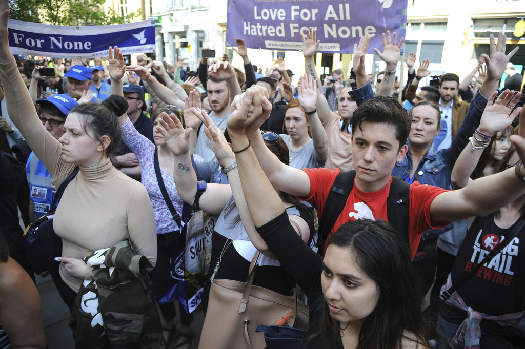 People gesture in solidarity during a vigil at St Ann's Square in central Manchester, England, Wednesday May 24 2017. British security ...