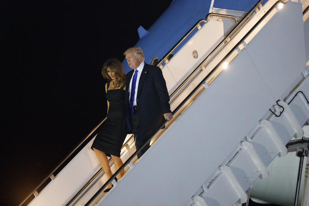President Donald Trump and first lady Melania Trump walk off Air Force One after arriving at Naval Air Station Sigonella, Thursday, May...