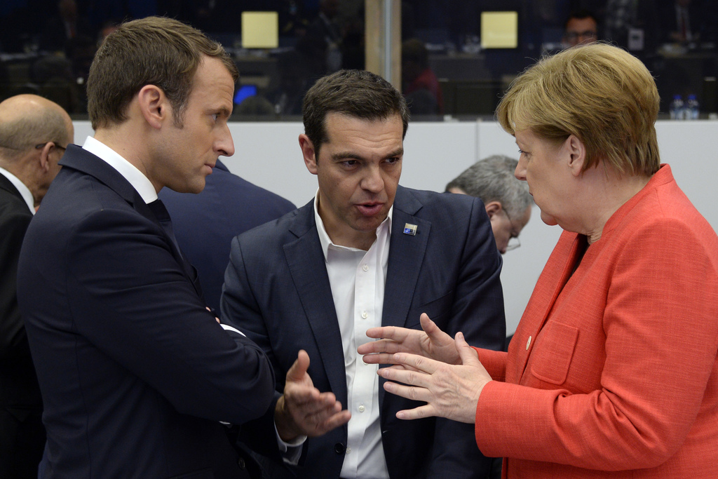 German Chancellor Angela Merkel, right and Greek Prime Minister Alexis Tsipras, centre  gesture as they speak with French President Emm...