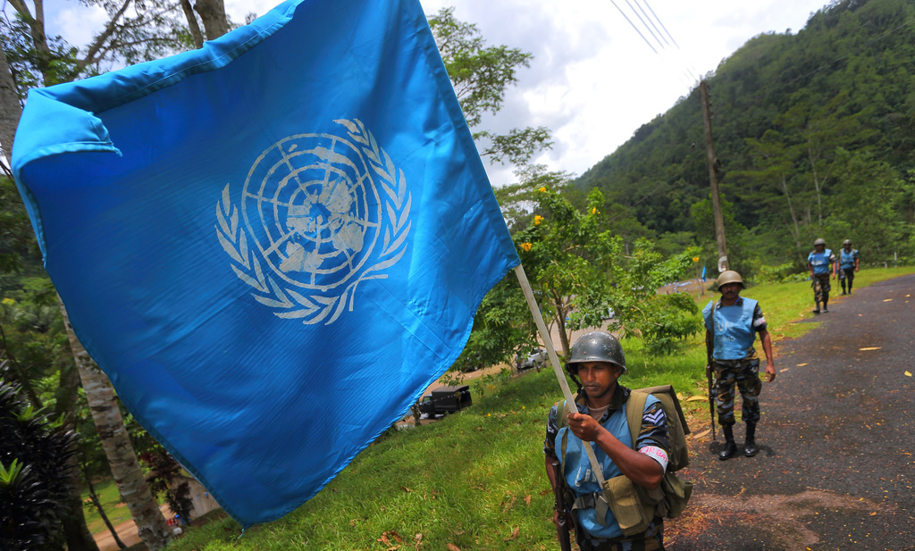 In this Sept. 13, 2016 photo, a Sri Lanka Air Force airman carries the U.N. flag during training for a road patrol at the Institute of ...