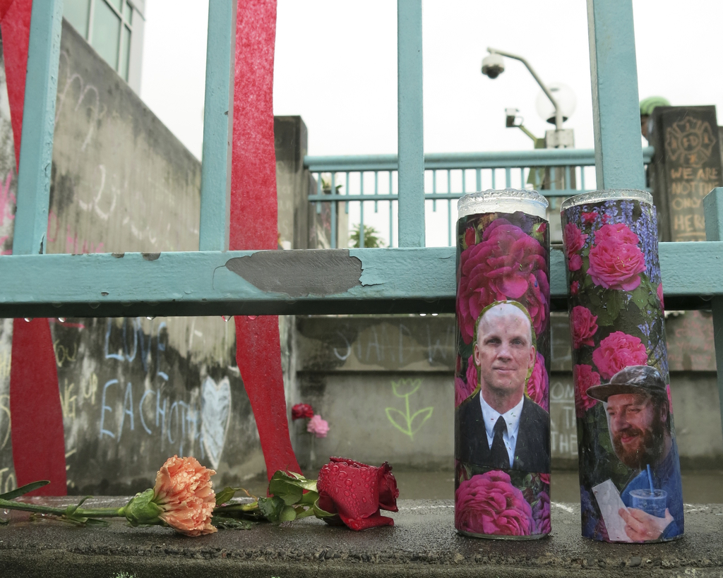 Votive candles bearing the photos of two men who were fatally stabbed on a Portland, Ore., light-train while trying to stop another man...