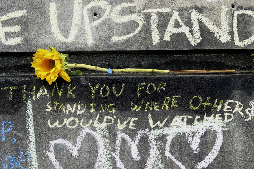 A flower and message are shown at a memorial in Portland, Ore., Tuesday, May 30, 2017, for the victims who were fatally stabbed while t...