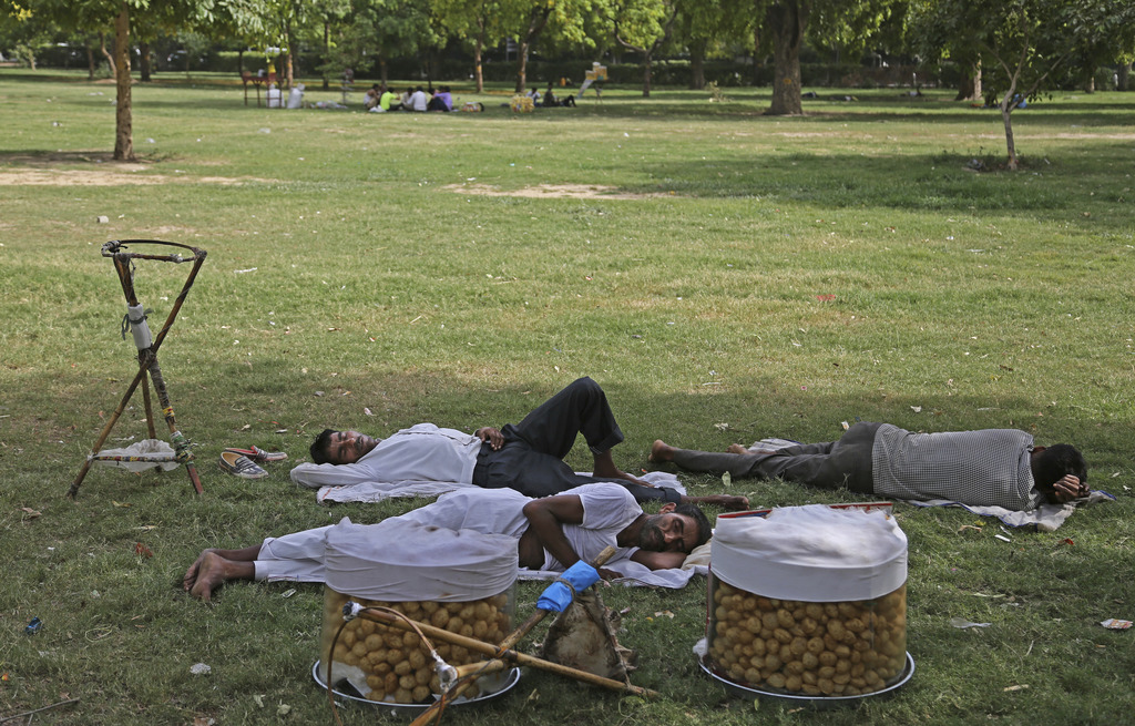 Indian snack vendors take an afternoon nap under the shade of a tree on a hot day in New Delhi, India, Tuesday, June 6, 2017. (AP Photo...