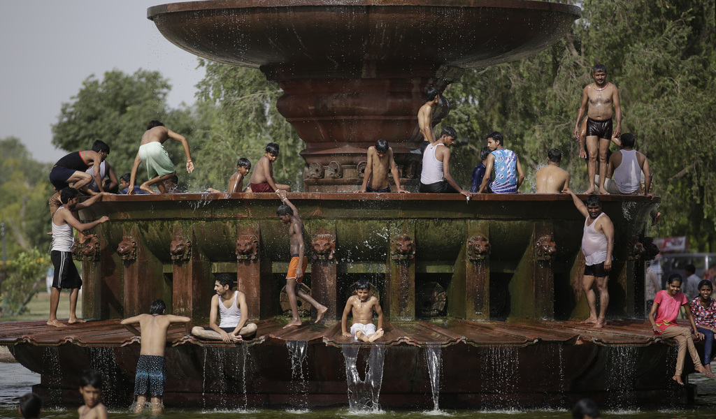 In this Thursday, June 6, 2017, file photo, Indians cool off themselves at a fountain near the India Gate monument on a hot day in New ...